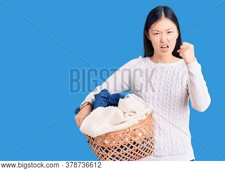 Young beautiful chinese woman holding laundry basket with clothes annoyed and frustrated shouting with anger, yelling crazy with anger and hand raised