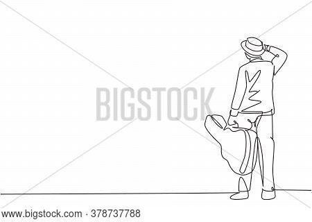 One Single Line Drawing Of Young Happy Male Guitarist Standing And Holding Acoustic Guitar Case. Dyn