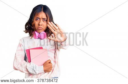 Young beautiful mixed race woman holding books wearing headphones with open hand doing stop sign with serious and confident expression, defense gesture