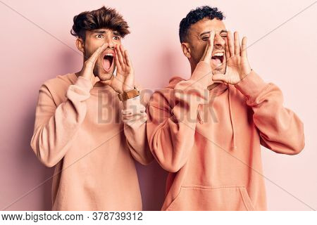Young gay couple wearing casual clothes shouting angry out loud with hands over mouth