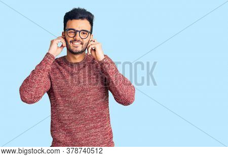Young handsome hispanic man wearing winter sweater and glasses covering ears with fingers with annoyed expression for the noise of loud music. deaf concept.