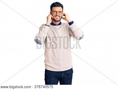 Young handsome hispanic man wearing elegant clothes and glasses covering ears with fingers with annoyed expression for the noise of loud music. deaf concept.