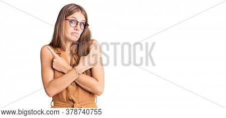 Young beautiful blonde woman wearing casual clothes and glasses pointing to both sides with fingers, different direction disagree