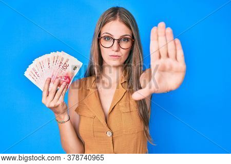 Young blonde girl holding israeli shekels with open hand doing stop sign with serious and confident expression, defense gesture