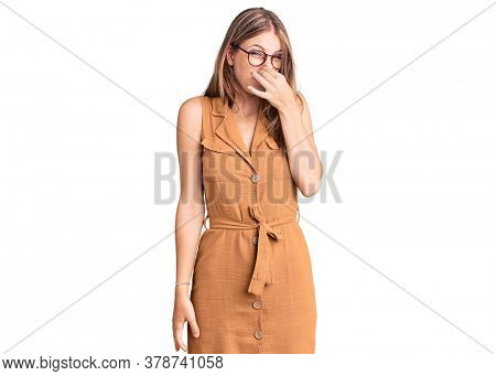 Young beautiful blonde woman wearing casual clothes and glasses smelling something stinky and disgusting, intolerable smell, holding breath with fingers on nose. bad smell