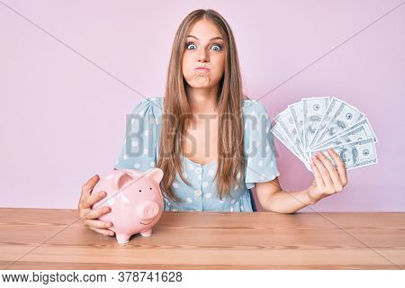 Young blonde woman holding dollars and piggy bank sitting on the table puffing cheeks with funny face. mouth inflated with air, catching air.