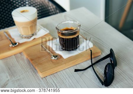 Black Coffee And Cappuccino In A Glass Cup On A Wooden Tray And Black Glasses. Morning Americano Wit