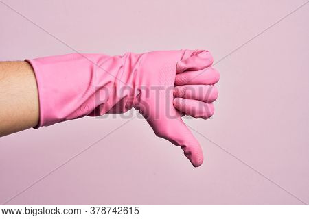 Hand of caucasian young man with cleaning glove over isolated pink background doing thumbs down rejection gesture, disapproval dislike and negative sign