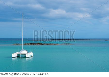 A Photography Of A Catamaran In The Ocean And Overcast Sky