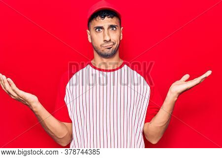 Young hispanic man wearing baseball uniform clueless and confused with open arms, no idea and doubtful face.