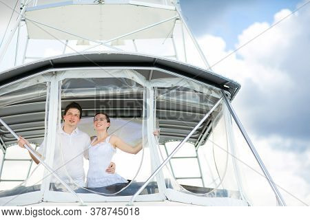 The Bride And Groom In White Wedding Clothes Travel On A Yacht At Sea. Honeymoon.