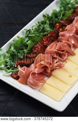 Plate with prosciutto cheese and sun-dried tomatoes