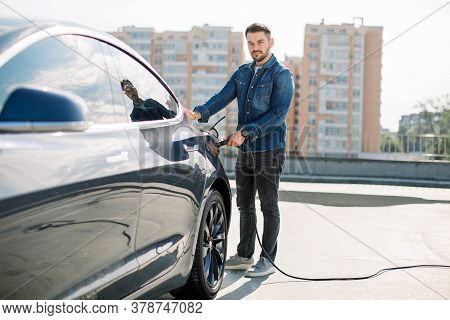 Full Length Portrait Of Young Handsome Bearded Man In Casual Wear, Standing At The Charging Station
