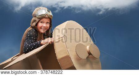 Cute dreamer girl playing with a cardboard airplane. Childhood. Fantasy, imagination. Studio portrait on a dark blue background.