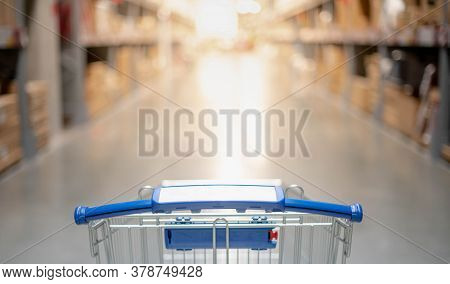 Blurred Effect In The Big Warehouse Aisle With Empty Silver And Blue Shopping Trolley, Shopper Choos