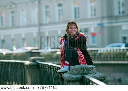 A young girl sits on the railing of the Griboedov canal embankment in Saint Petersburg.