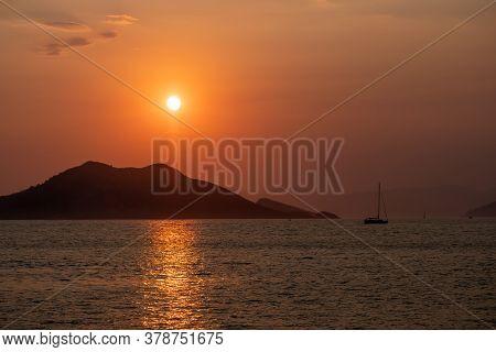 Boat At Sea While Sun Sets And Island
