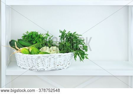 Green Autumn Vegetables In Basket On Shelf In Wooden Rack Near A White Wall. Copy Space For Putting