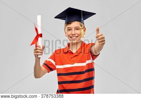 school, education and graduation concept - portrait of happy smiling graduate student boy in bachelor hat or mortarboard with diploma over grey background