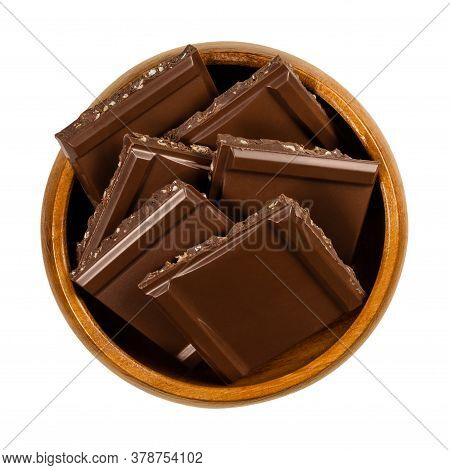 Dark Nut Chocolate, Cut Into Square Shaped Pieces, In A Wooden Bowl. Black Chocolate With Fine Nut B