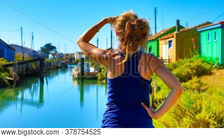 Woman looking at beautiful multicolored oyster sheds at Oleron Island