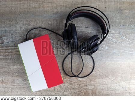 Headphones And Book. The Book Has A Cover In The Form Of Monaco Flag. Concept Audiobooks. Learning L