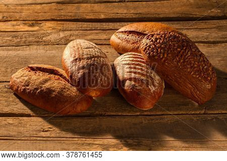 Bread On Rustic Wooden Background. Whole Freshly Baked Artisan Bread.