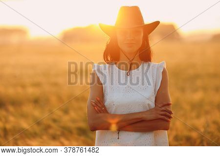 Woman Farmer In Cowboy Hat At Agricultural Field On Sunset With Sunflare
