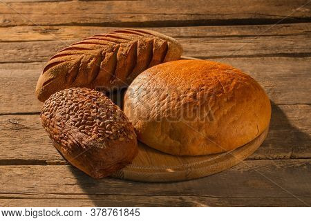Three Loaves Of Homemade Bread On Cutting Board. Fresh Artisan Bread On Wooden Background. Rustic St