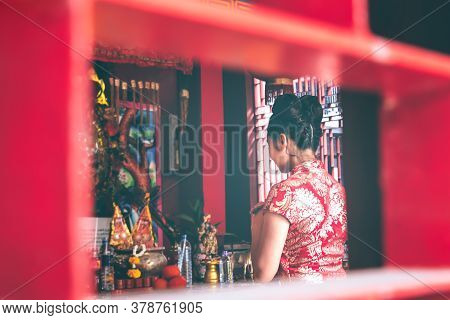 Blurred Soft Images Of An Asian Women Wearing A Red Cheongsam Standing In A Shrine To Pay Respect To