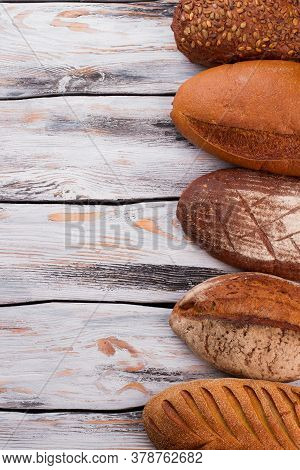 Wholemeal Bread Loaves And Copy Space. Fresh Bread On Vintage Wooden Background. Space For Text.
