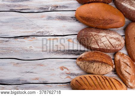 Delicious Homemade Bread And Copy Space. Artisan Bread On Rustic Wooden Background.