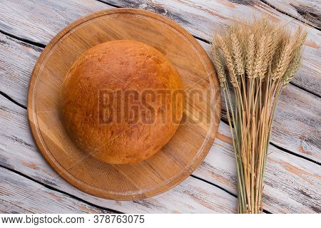 Round Bread With Wheat Ears On Wooden Background. Loaf Of Artisan Bread On Wooden Table. Rustic Stil