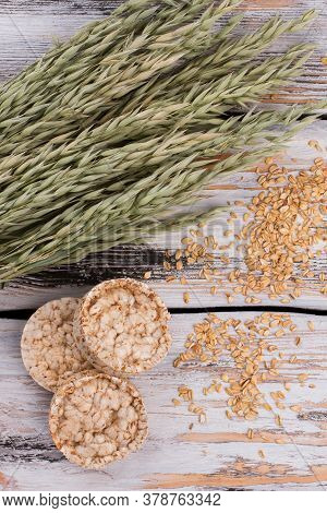 Oat Flakes, Spikelets And Crunchy Crispbread. Multi-grain Crispbreads With Grains And Ears On Wooden