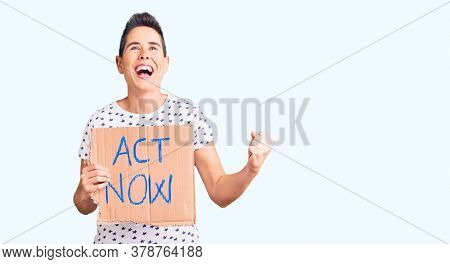 Young woman with short hair holding act now banner screaming proud, celebrating victory and success very excited with raised arms
