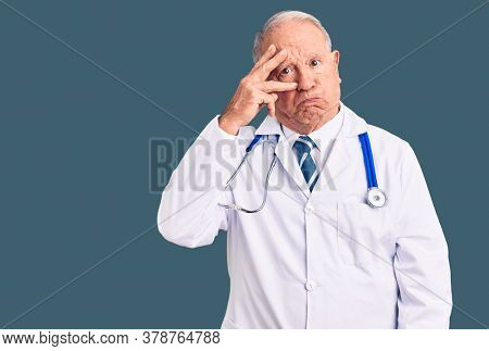Senior handsome grey-haired man wearing doctor coat and stethoscope worried and stressed about a problem with hand on forehead, nervous and anxious for crisis