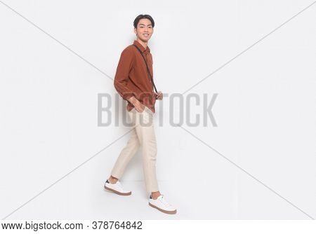 Full body Young Man in Khakis and Long Sleeve brown Shirt standing with white sneakers runway in studio