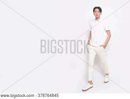 Full body Young handsome man with wearing white polo shirt with white jeans pants runway in studio