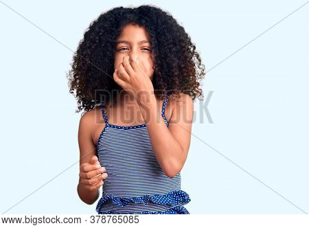 African american child with curly hair wearing swimwear smelling something stinky and disgusting, intolerable smell, holding breath with fingers on nose. bad smell