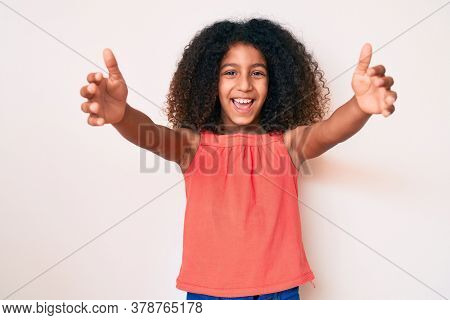 African american child with curly hair wearing casual clothes looking at the camera smiling with open arms for hug. cheerful expression embracing happiness.