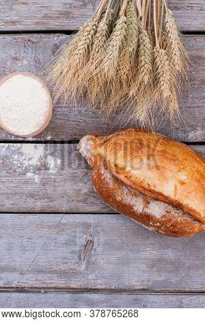 Wheat Ears, Fresh Bread And Bowl With Flour. Homemade Bread, Wheat Ears And Flour On Wooden Boards B