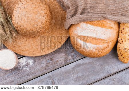 Peasant Bread On Wooden Background. Straw Hat, Homemade Bread And Bowl With Flour. Peasant Labor Con