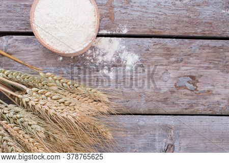 Bowl With Flour And Ears Of Wheat. Ears Of Wheat And Bowl Of Flour On Rustic Wooden Boards. Space Fo