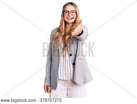 Young beautiful blonde woman wearing call center agent headset smiling friendly offering handshake as greeting and welcoming. successful business.