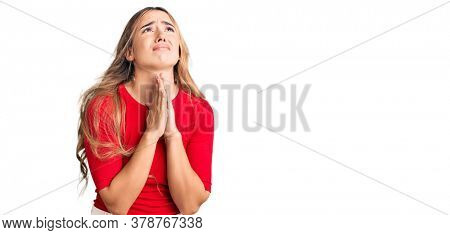 Young beautiful blonde woman wearing casual clothes begging and praying with hands together with hope expression on face very emotional and worried. begging.
