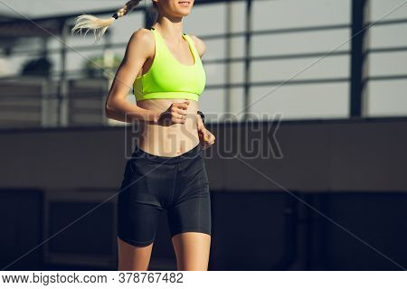 Strong. Female Runner, Athlete Training Outdoors. Professional Runner, Jogger Working Out On The Str