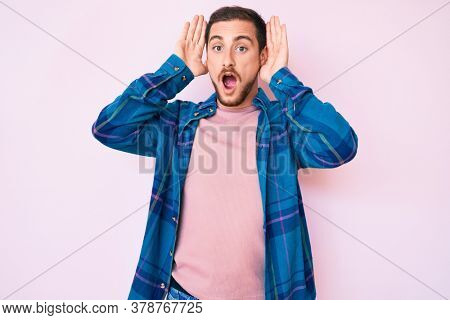 Young handsome man wearing casual clothes smiling cheerful playing peek a boo with hands showing face. surprised and exited