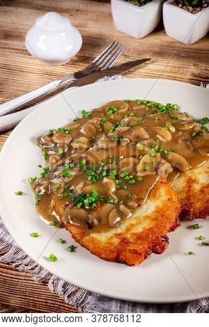 Crispy Potato Pancakes With Mushroom Sauce On Wooden Table.