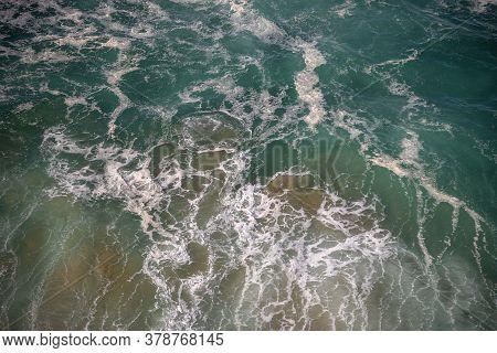 Wild Blue Ocean Water Smashing The Coast Picking Up Brown Sand An Creating White Foam