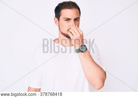 Young handsome man wearing casual white tshirt smelling something stinky and disgusting, intolerable smell, holding breath with fingers on nose. bad smell